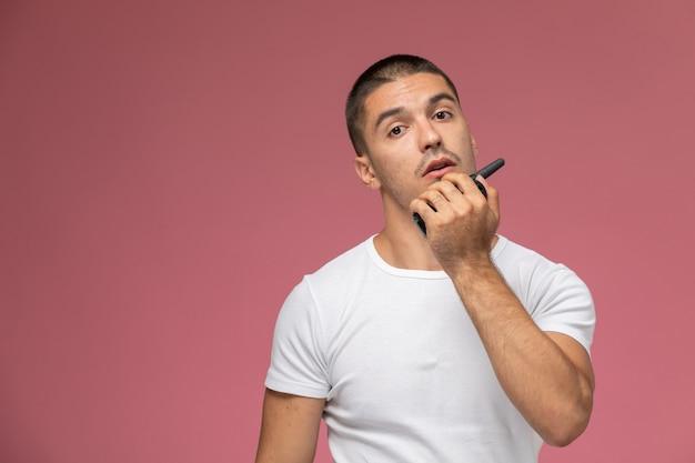Vooraanzicht jonge man in wit t-shirt met walkie-talkie op roze bureau
