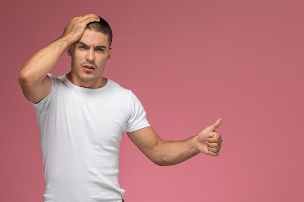 Vooraanzicht jonge man in wit t-shirt met zijn hoofd op roze achtergrond