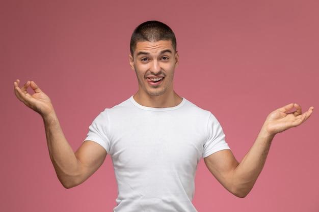 Vooraanzicht jonge man in wit t-shirt poseren en mediteren op roze achtergrond