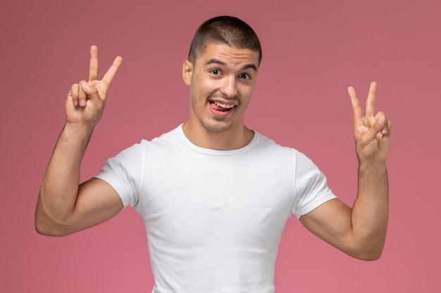Vooraanzicht jonge man in wit t-shirt poseren met overwinningstekens op roze achtergrond