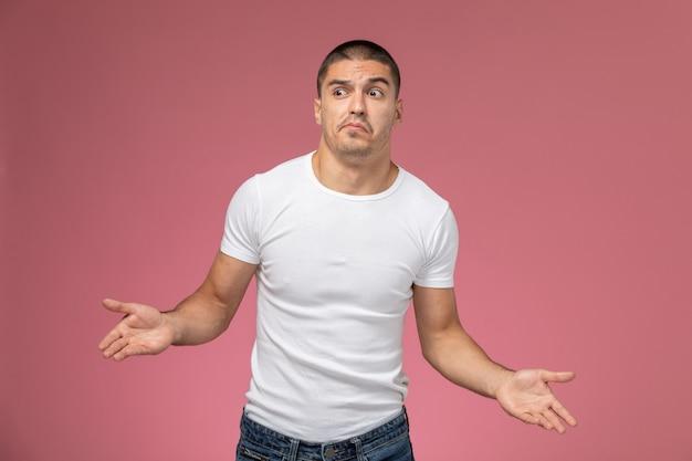 Vooraanzicht jonge man in wit t-shirt poseren met verwarde uitdrukking op de roze achtergrond