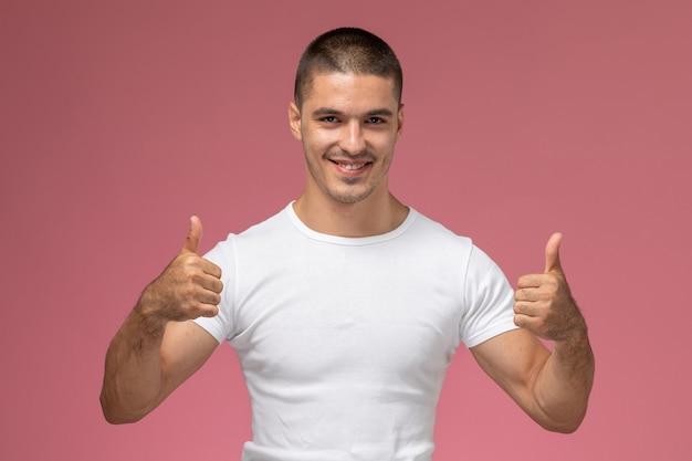 Vooraanzicht jonge man in wit t-shirt poseren weergegeven: als borden op roze achtergrond