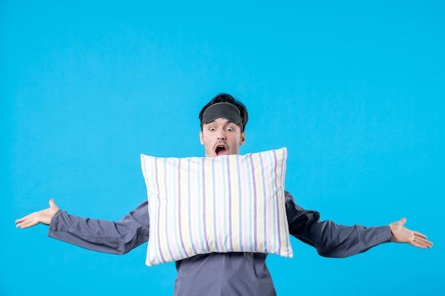 Vooraanzicht jonge man in zijn pyjama kussen op blauwe achtergrond kleur nachtmerrie menselijk bed droom nachtrust wakker laat slapen
