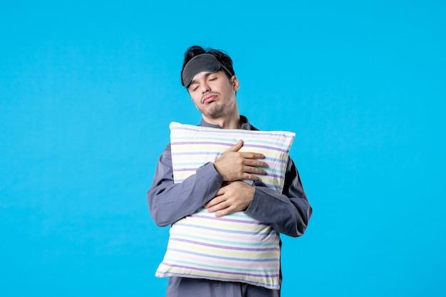 Vooraanzicht jonge man in zijn pyjama met kussen op blauwe achtergrond menselijk droom slaap nacht kleur laat bed rust nachtmerrie wakker slapen
