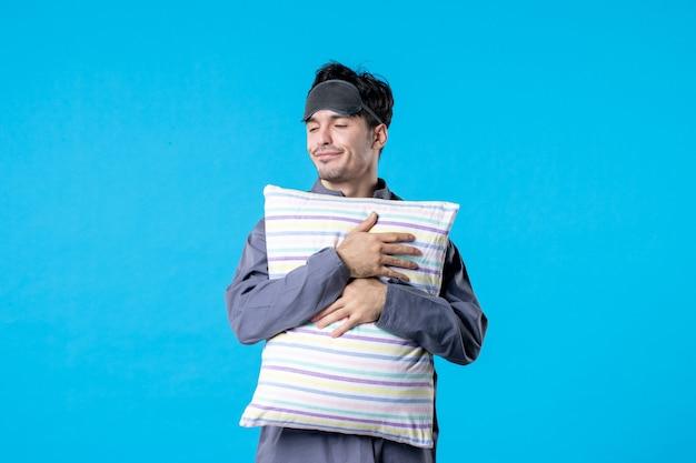 Vooraanzicht jonge man in zijn pyjama met kussen op blauwe achtergrond menselijk droom slaap nacht kleuren laat bed rust nachtmerrie wakker