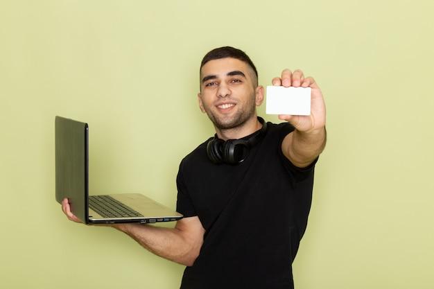 Vooraanzicht jonge man in zwart t-shirt glimlachend en met behulp van laptop met witte kaart op groen