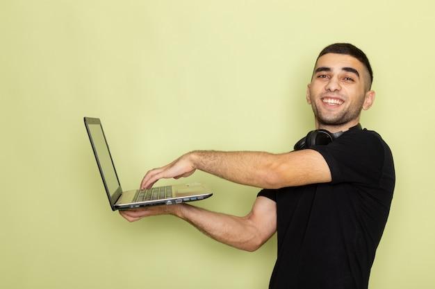 Vooraanzicht jonge man in zwart t-shirt glimlachend en met behulp van sterke laptop op groen
