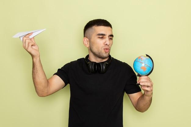 Vooraanzicht jonge man in zwart t-shirt met papieren vliegtuigje en kleine wereldbol op groen