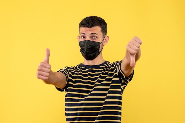 Vooraanzicht jonge man in zwart-wit gestreept t-shirt duim op en neer ondertekenen op gele achtergrond