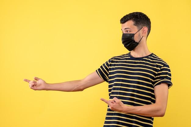 Vooraanzicht jonge man in zwart-wit gestreepte t-shirt gele achtergrond kopie plaats