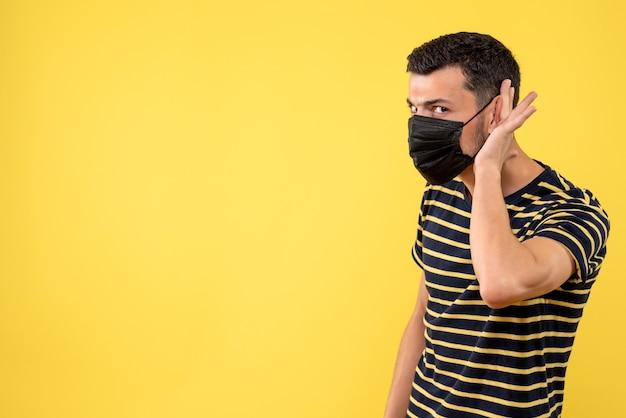 Vooraanzicht jonge man in zwart-wit gestreepte t-shirt luisteren naar iets gele achtergrond