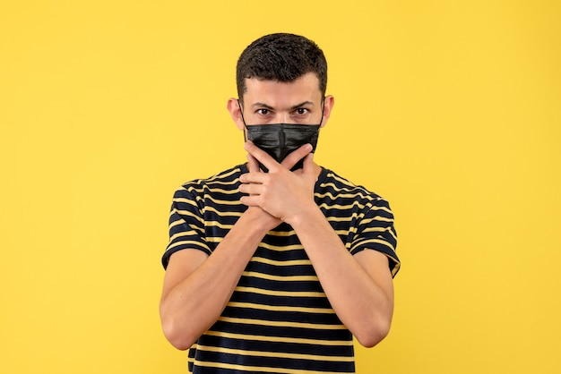 Vooraanzicht jonge man in zwart-wit gestreepte t-shirt met kin gele geïsoleerde achtergrond
