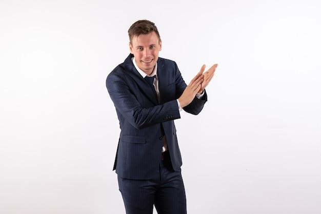 Vooraanzicht jonge man klappen in klassieke strikte pak op witte achtergrond emoties menselijke mannelijke pak mannequin