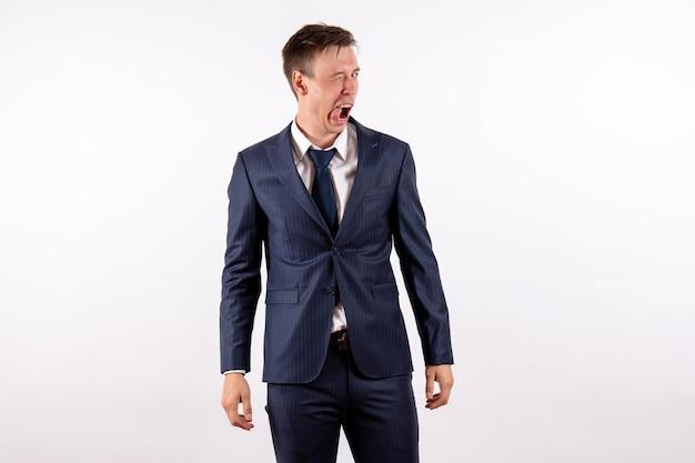 Vooraanzicht jonge man knipogen op een grappige manier in klassiek strikt pak op witte achtergrond