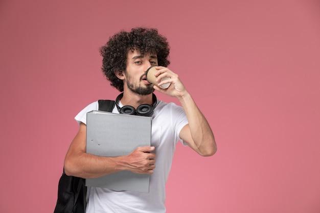 Vooraanzicht jonge man koffie drinken en bindmiddel te houden