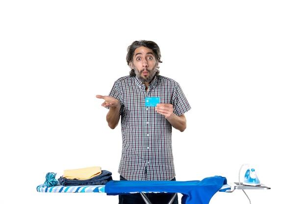 Vooraanzicht jonge man met bankkaart achter strijkplank op witte achtergrond foto strijken huishoudelijk werk machine man huis schoonmaken geld