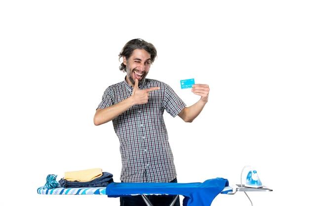 Vooraanzicht jonge man met bankkaart achter strijkplank op witte achtergrond ijzeren machine thuis geld huishoudelijk werk man droge was
