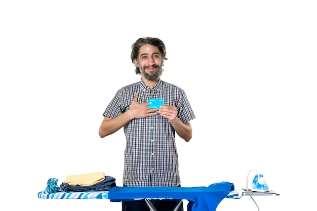 Vooraanzicht jonge man met bankkaart achter strijkplank op witte achtergrond kleurenfoto strijken huishoudelijk werk machine huis schoonmaken