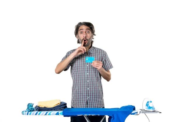 Vooraanzicht jonge man met bankkaart achter strijkplank op witte achtergrond kleurenfoto strijken huishoudelijk werk machine man huis schoonmaken geld