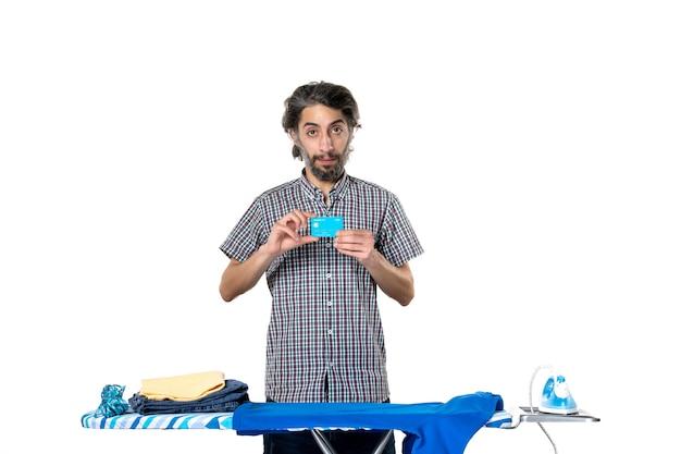 Vooraanzicht jonge man met bankkaart achter strijkplank op witte achtergrond kleurenfoto strijken huishoudelijk werk machine man huis schoonmaken
