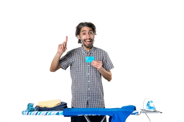 Vooraanzicht jonge man met bankkaart achter strijkplank op witte achtergrond kleurenfoto strijken huishoudelijk werk man huis schoonmaken