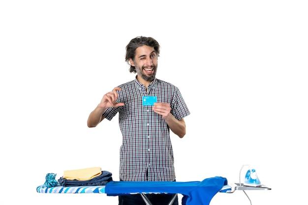 Vooraanzicht jonge man met bankkaart achter strijkplank op witte achtergrond kleurenfoto strijkmachine man huis schoonmaken