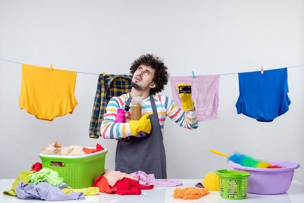 Vooraanzicht jonge man met bankkaart en shampoos op witte muur