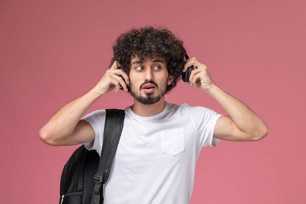 Vooraanzicht jonge man met behulp van een kant van de hoofdtelefoon om lied te luisteren