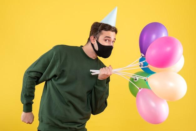 Vooraanzicht jonge man met blauwe feestmuts en kleurrijke ballonnen staande op geel