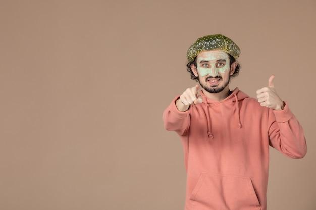 Vooraanzicht jonge man met bouffant pet en masker op zijn gezicht op bruine achtergrond spa huidverzorging gezichtshaar huidtherapie