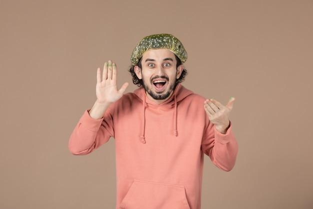 Vooraanzicht jonge man met bouffant pet op bruine achtergrond salon huidverzorging masseren huidtherapie gezichtsspa