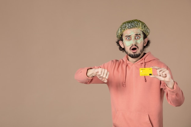 Vooraanzicht jonge man met creditcard op bruine achtergrond spa lichaamsverzorging geld therapie huidverzorging salon gezichtshuid