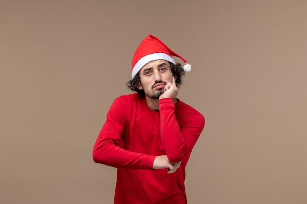 Vooraanzicht jonge man met denken gezicht op bruin bureau emotie kerstvakantie