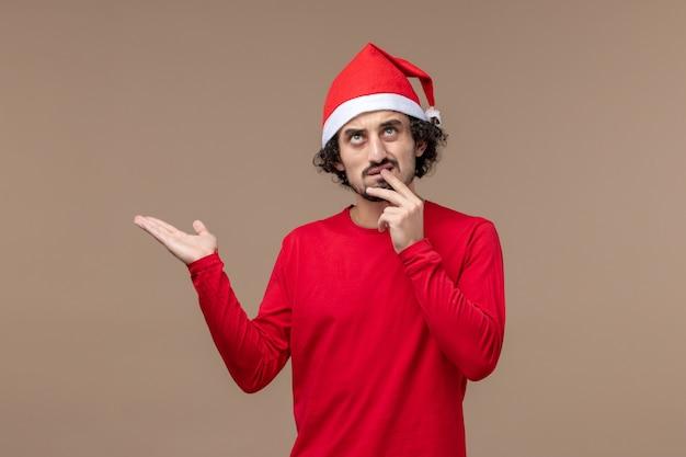 Vooraanzicht jonge man met denken gezicht op bruine achtergrond vakantie emoties kerst