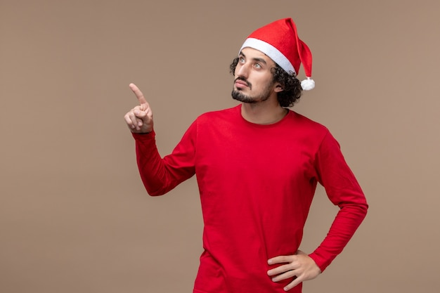 Vooraanzicht jonge man met denken gezicht op bruine achtergrond vakantie kerst emoties