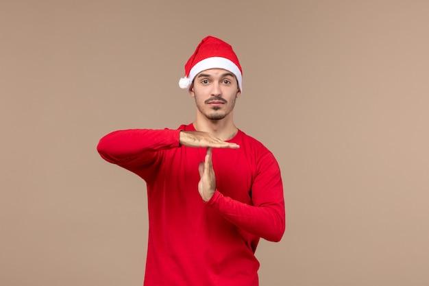 Vooraanzicht jonge man met denken uitdrukking op een bruine achtergrond emotie kerstvakantie