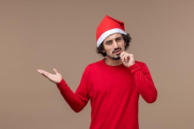 Vooraanzicht jonge man met denken uitdrukking op een bruine achtergrond vakantie emoties kerst