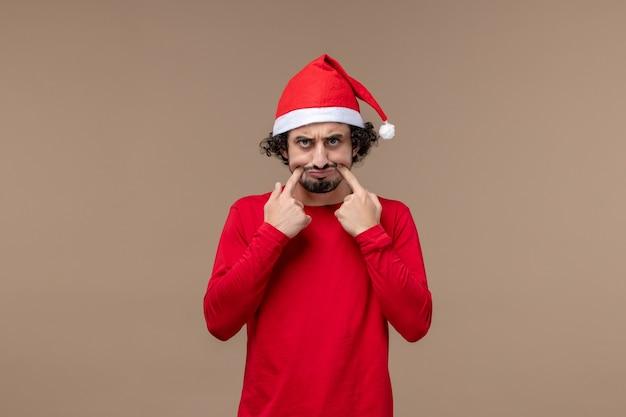 Vooraanzicht jonge man met droevig gezicht op bruine achtergrond emotie kerstvakantie