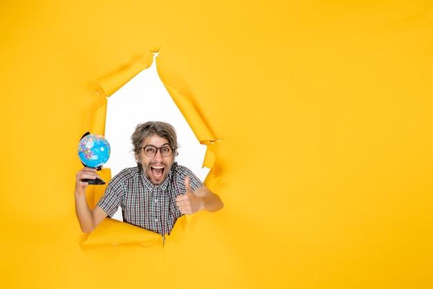 Vooraanzicht jonge man met earth globe op gele achtergrond kleur emotie kerst planeet vakantie wereld land