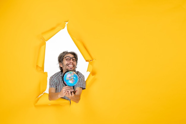 Vooraanzicht jonge man met earth globe op gele achtergrond kleur kerst planeet vakantie wereld land emotie
