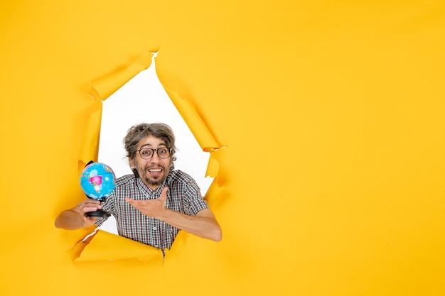 Vooraanzicht jonge man met earth globe op gele achtergrond land planeet emotie wereld vakantie kerst kleur