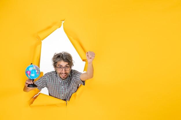 Vooraanzicht jonge man met earth globe op gele achtergrond land planeet emotie wereld vakantie kleur
