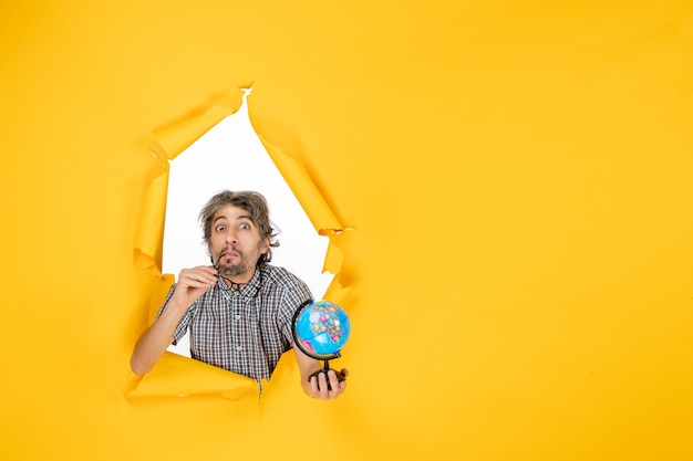 Vooraanzicht jonge man met earth globe op gele achtergrondkleur kerst planeet vakantie land emotie