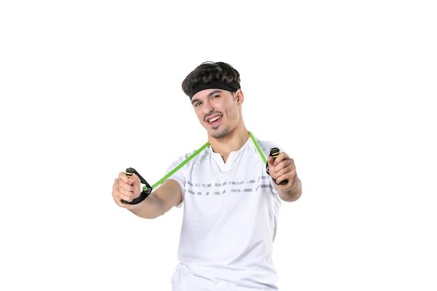 Vooraanzicht jonge man met expander op witte achtergrond fit atleet sportschool dieet lichaam levensstijl ziekenhuis regime