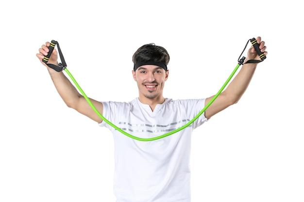 Vooraanzicht jonge man met expander op witte achtergrond fit atleet sportschool dieet sport lichaam levensstijl ziekenhuis regime