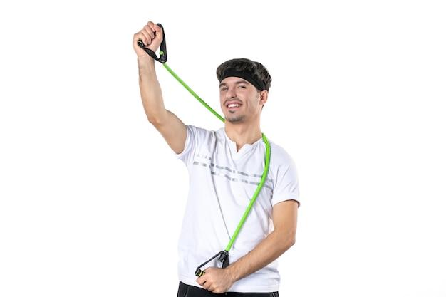 Vooraanzicht jonge man met expander op witte achtergrond fit atleet sportschool dieet sport lichaam ziekenhuis regime