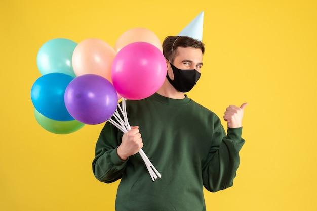 Vooraanzicht jonge man met feest pet houden ballonnen staande op gele achtergrond