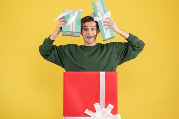 Vooraanzicht jonge man met feestmuts en geschenken staan achter grote geschenkdoos op gele achtergrond