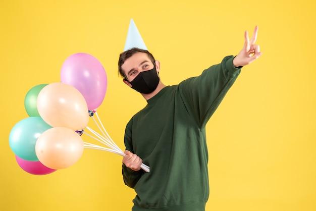 Vooraanzicht jonge man met feestmuts en kleurrijke ballonnen maken overwinningsteken staande op geel