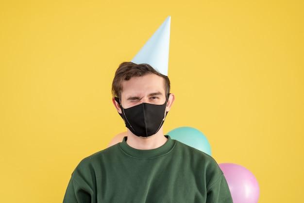 Vooraanzicht jonge man met feestmuts en zwart masker op geel